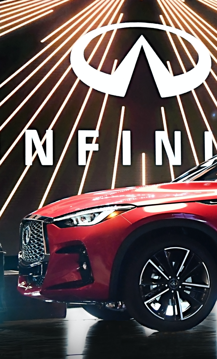 Front and side view of a luxurious red 2022 INFINITI QX55 crossover