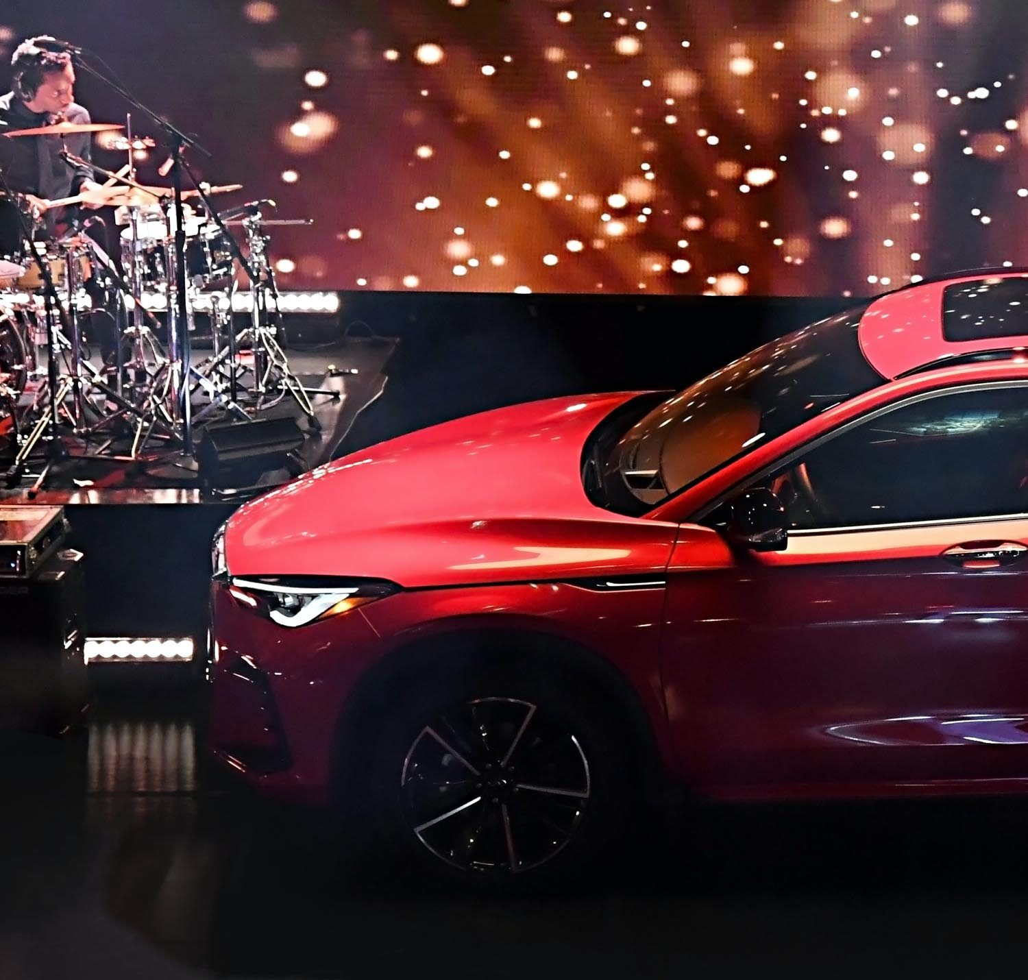 The hood and front of a red new 2022 INFINITI QX55 crossover on stage.