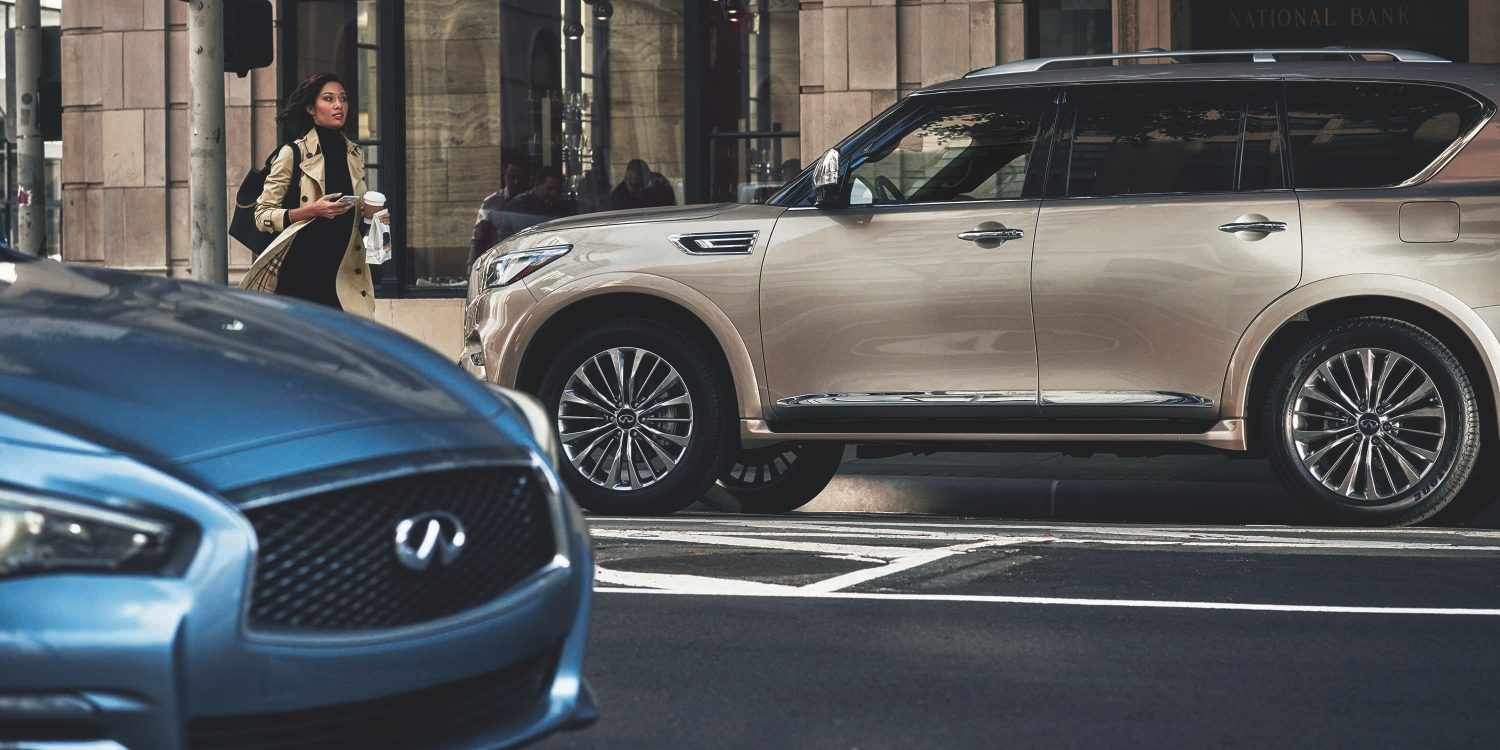 Side profile of a 2021 INFINITI QX80 SUV driving on the road