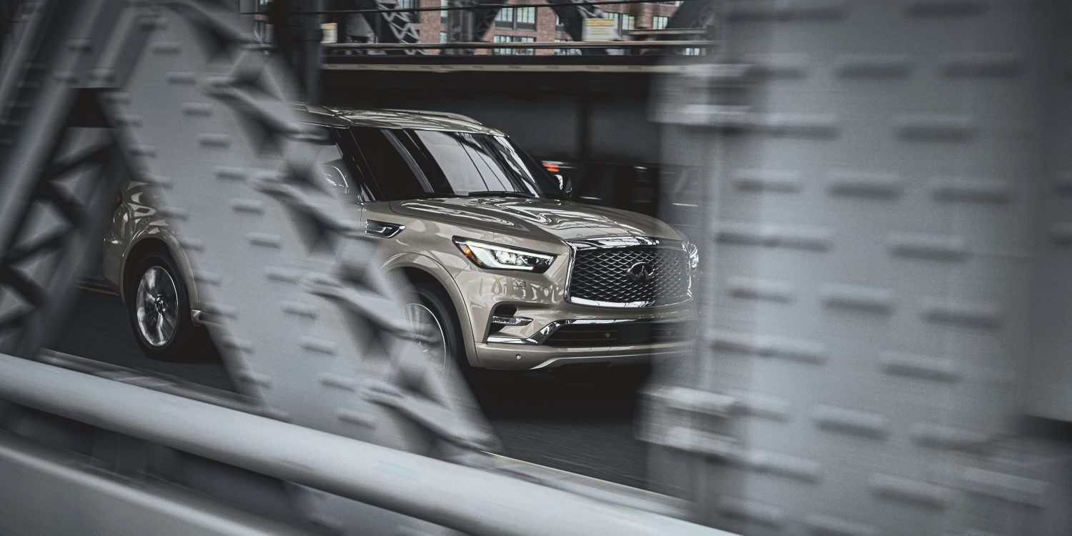 Side profile of a 2021 INFINITI QX80 SUV driving fast on the road