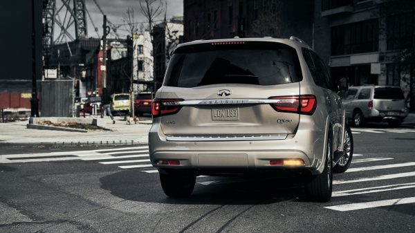 Rear view of a 2021 INFINITI QX80 SUV making a right turn on the road