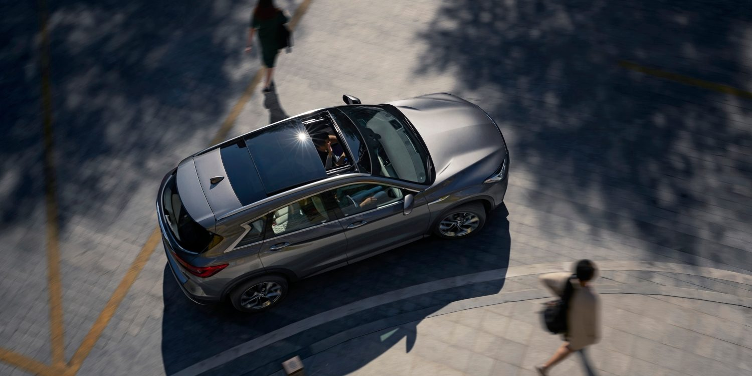 INFINITI QX50 from above with people walking beside it