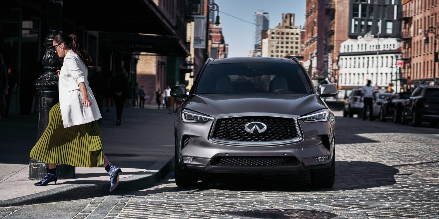 A women crossing the road in front of a 2019 INFINITI QX50