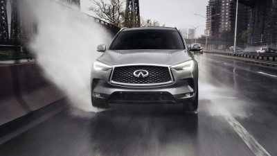 2020 INFINITI QX50 Luxury Crossover Driving In Wet Conditions Causing A Water Splash To The Sidewalk